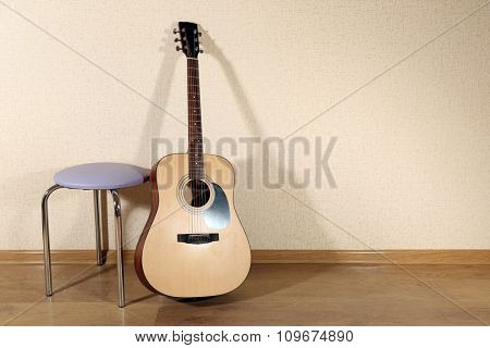 Acoustic guitar propped on wall with stool in the room