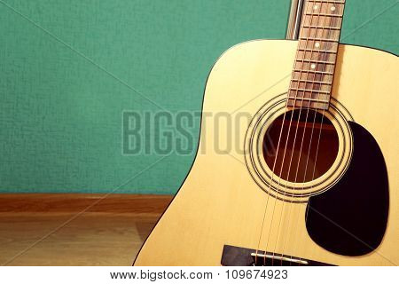 Guitar on the floor against blue background in the studio, close up
