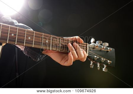 Guitars neck in musician hands on dark background, close up