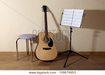 Acoustic guitar propped on wall with stool and musical notes holder in the room