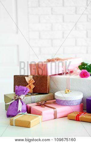 Decorated gift boxes and flowers on the table in front of white brick wall background