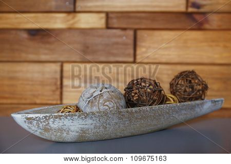 Beautiful composition of wattled balls on grey table against wooden background