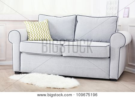 Gray sofa with colorful pillows in room