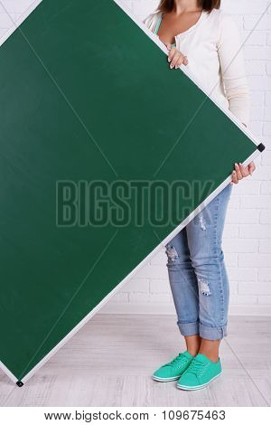Woman in causal with green blackboard against brick wall, close up