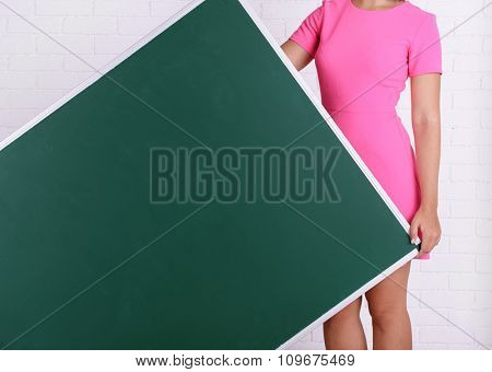 Woman in pink dress with green blackboard against brick wall, close up