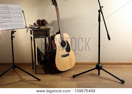 Acoustic guitar propped on wall with stool and headphones on it in the room, close up