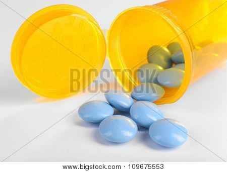 Blue drugs spilled from yellow pill bottle on white background, close up