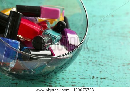 Nail polish set in bowl on wooden table closeup