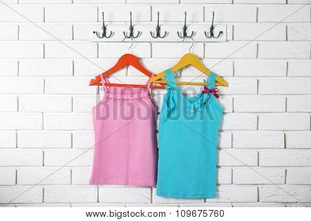 Child clothes on hanger on white wall background