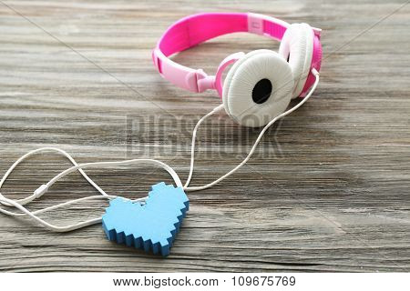 Pink headphones with blue heart on wooden background