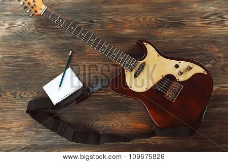 Electric guitar with notebook on wooden table close up