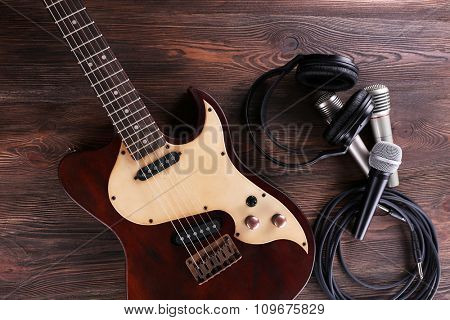 Electric guitar with microphones and headphones on wooden table close up