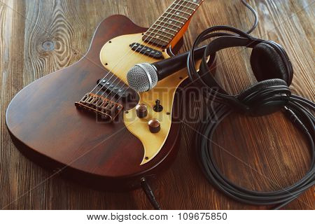 Electric guitar with microphone and headphones on wooden table close up