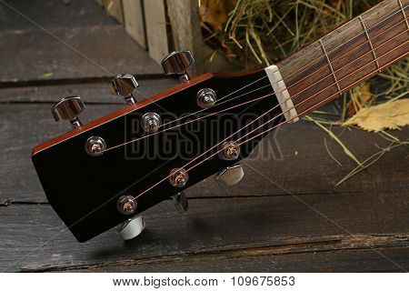 Acoustic guitar against box with hay on wooden background,, close up