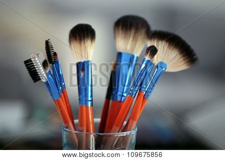 Cosmetic brushes in glass on bright background