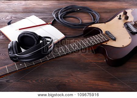 Electric guitar with headphones and notebook on wooden table close up
