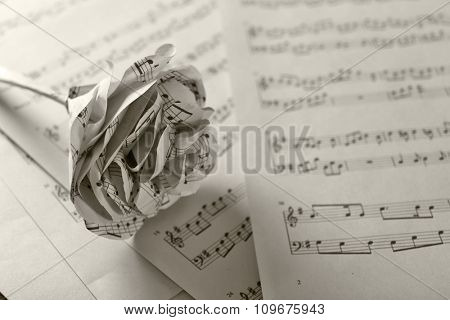 Single white paper-made rose on musical notes pages background