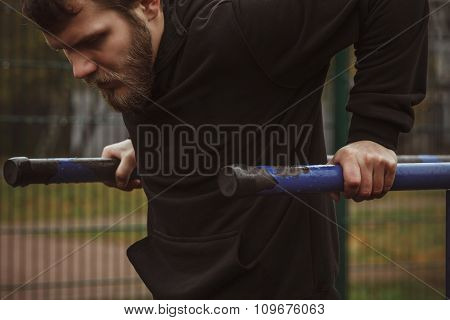 Muscular man during his workout on the street