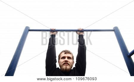 young man doing pull ups on horizontal bar outdoors