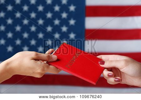 One hand giving the passport to another on American Flag background