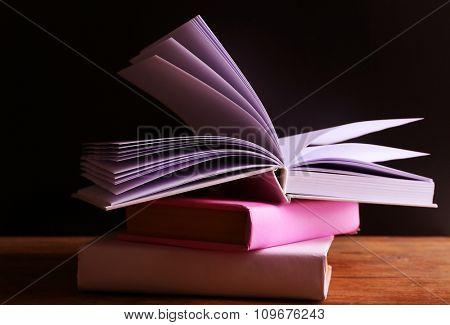 Pile of books on wooden table against black background