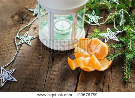 Christmas composition: lantern, candle, tangerine, garland and s