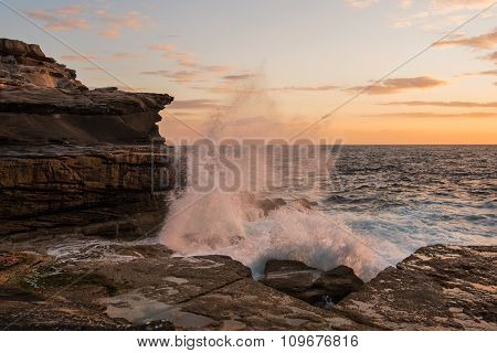 Orange Crashing Wave Over Cliffs