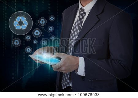 Businessman hand touch screen recycle sign icons on a tablet.