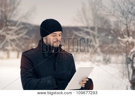 Man with Tablet Outside in Winter Decor