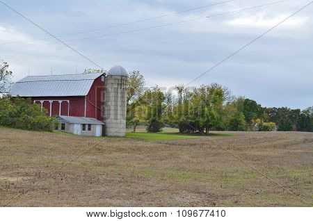 Red barn with silo and plowed field