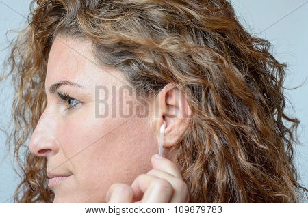 Woman Cleaning Her Ear With A Cotton Swab