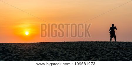 Man In Silhouette Standing At Tropical Beach