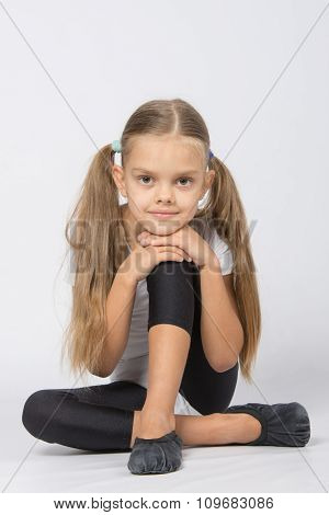 Girl Gymnast Sitting On The Floor With His Pen On His Knee