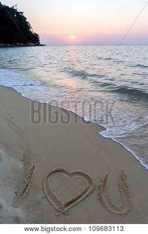 I love you symbol written on sandy beach at sunset