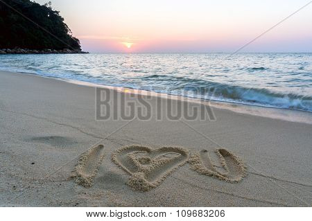 I love you symbol written on sandy beach at sunset