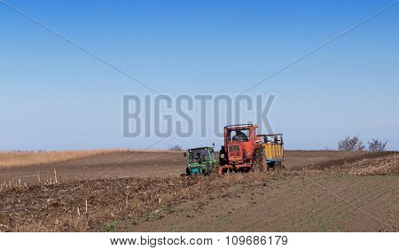 Two Tractors Working On Fertilizing Field