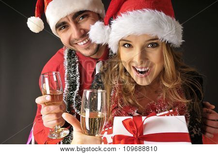 Funny Christmas Couple With Glasses Of Champagne  Covering Dark Background