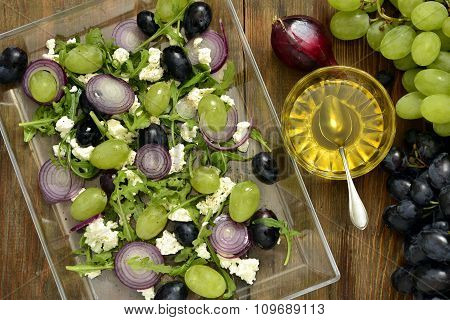 Salad with various grapes, goat cheese, purple onion, arugula