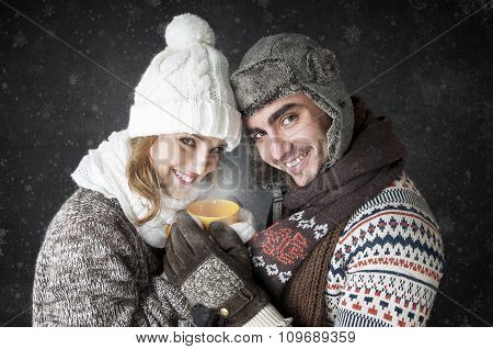 Happy Young Couple  With A Cup Of Tea Covering  Snow Background