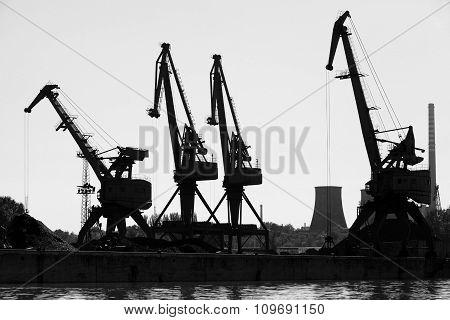 Dark Silhouettes Of Industrial Port Cranes. Danube River