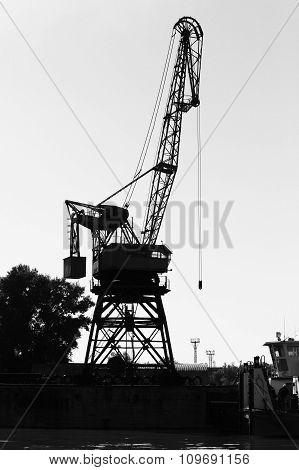 Dark Silhouette Of Industrial Port Crane. Danube River