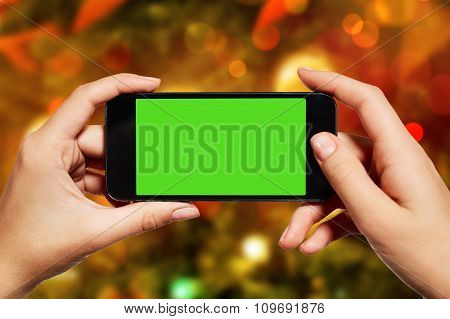 Isolated Woman Hand Holding The Smart Phone With Isolated Green Screen Against Christmas Or New Year