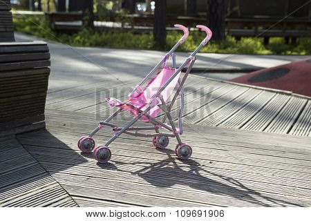 Pink pram stands alone in the park.