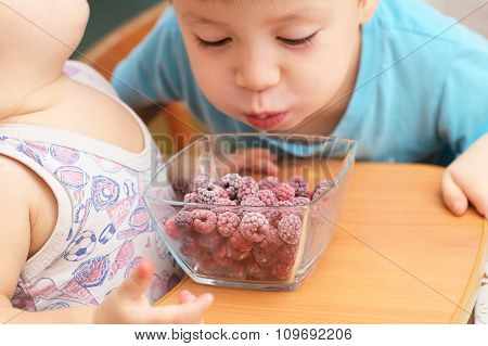 Boy Blowing On Frozen Rasberries For Heating