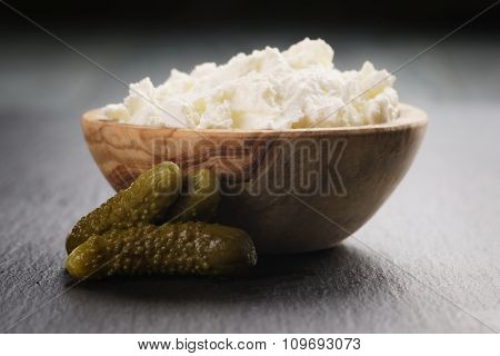 ricotta cheese in wooden bowl with marinate cucumbers
