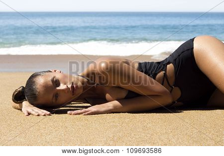 Fashion beautiful woman in bikini lying on beach near sea enjoying looking view of tropics. Hot summ
