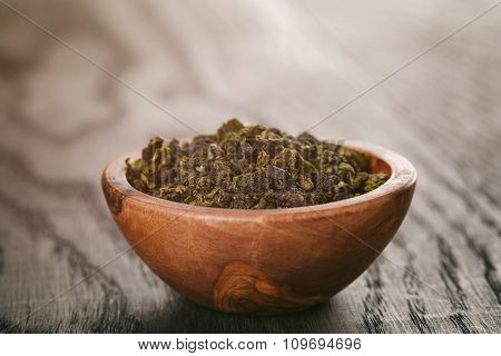 oolong green tea in wood bowl on oak table