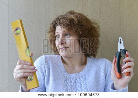 woman is holding construction tools