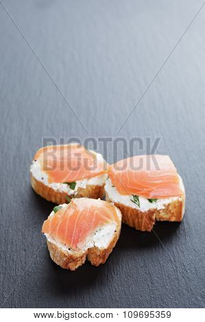 baguette slices with soft cheese and salmon on slate board