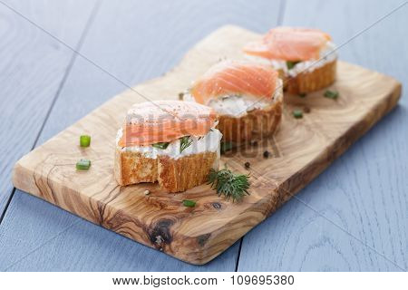 baguette slices with soft cheese and salmon on wood table